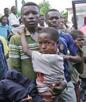 A Somali man carries a boy wounded during mortar shelling