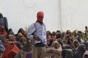 An Al Shabaab soldier stands next to women during food distribution at a displaced persons camp in Shebelle