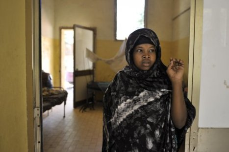 A young woman stands by the door way of a hospital in Belet Weyne