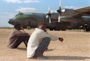 Two Somali men sit on the runway at Belet Weyn, Somalia in 1992