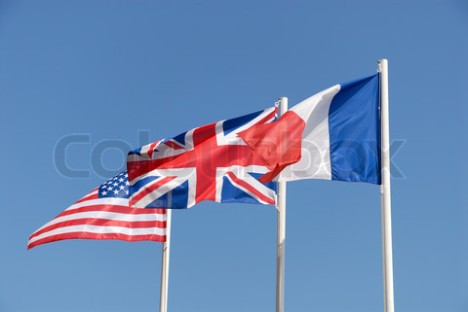 National flags of UK, USA and France against blue sky