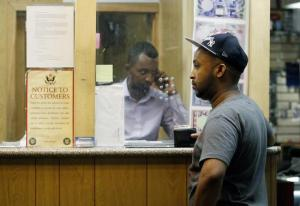 Ahamed waits as Hussein, owner of money transfer business Mustaqbal Express in Minneapolis, wires money to his ex-wife in Somalia